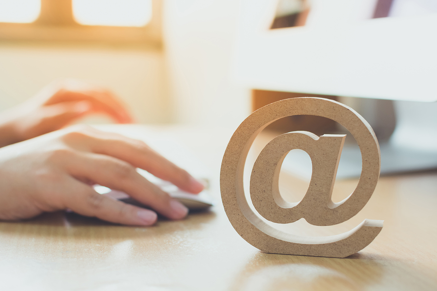 Email marketing concept, Hand using computer sending message with wooden email address symbol
