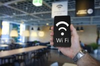 Free Wi-Fi. Modern smartphone in hand of man in cafe with free wifi. Man connecting smartphone to Wifi zone in cozy cafe. badge and the inscription of wi fi in black phone