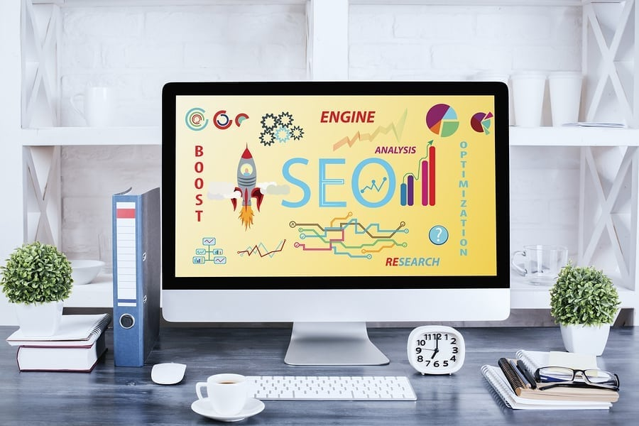 Front view of creative designer desktop with SEO web page on computer screen. Startup concept